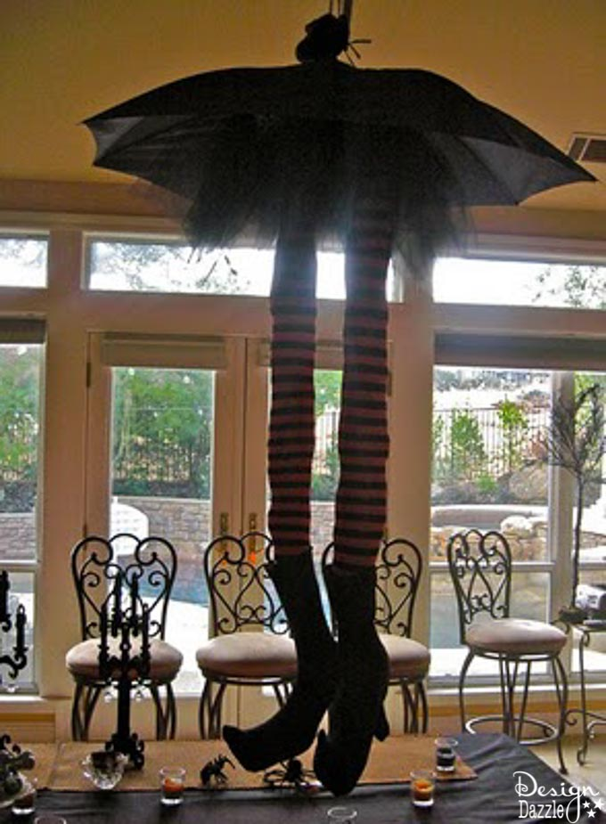 These adorable striped whimsical witch legs hang from the ceiling to make an adorable centerpiece for any Halloween Party! | Design Dazzle