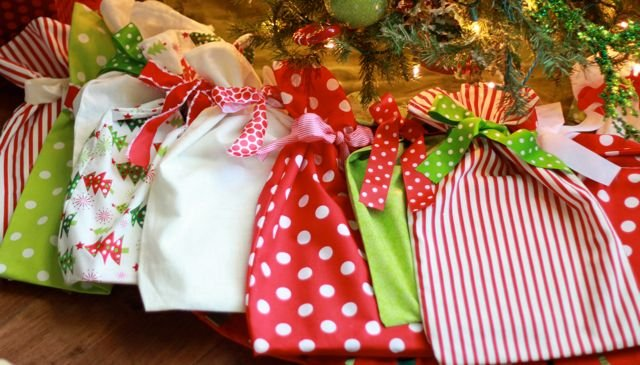 Christmas Book Bags: They look like Christmas presents already wrapped and under the tree. Every one of these fabric bags has a Christmas book inside. Great way to countdown to Christmas or have your child pick a bag to find the surprise book for the night! - Design Dazzle #christmas #christmasbooks