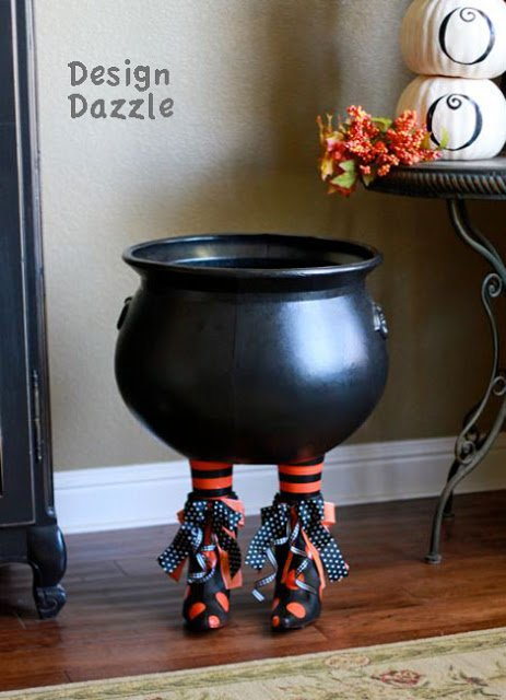 Make an unusual Halloween prop for your decor! Add witch's boots to a plastic cauldron for a Boot-a-licious Halloween decor! - Design Dazzle