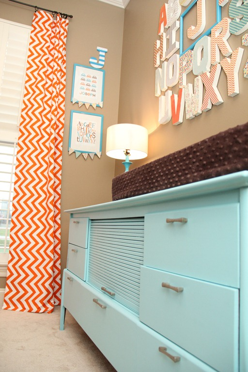 orange and turquoise baby nursery changing table