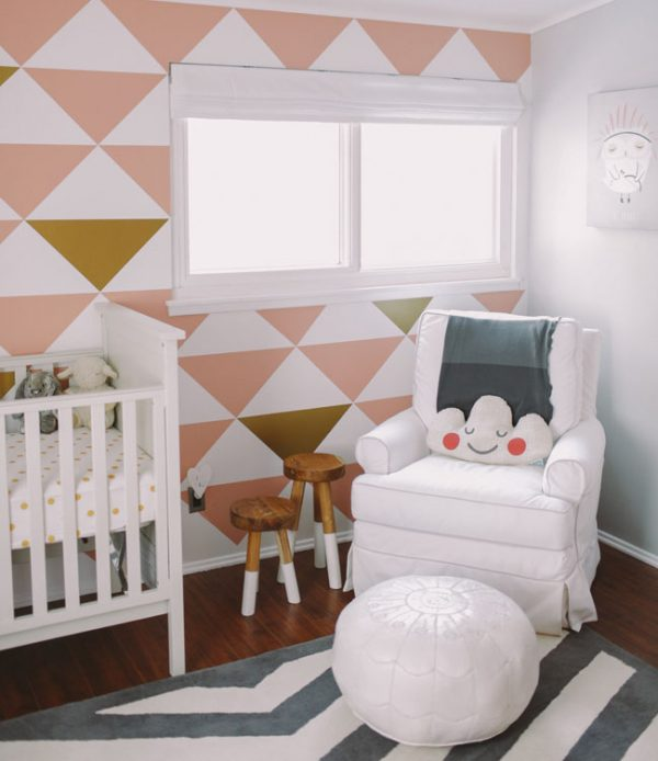 Pretty pink and gold colored triangles on this accent wall in a nursery