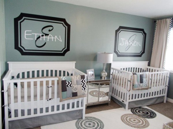 Painted names or monograms above each crib in a nursery for twins