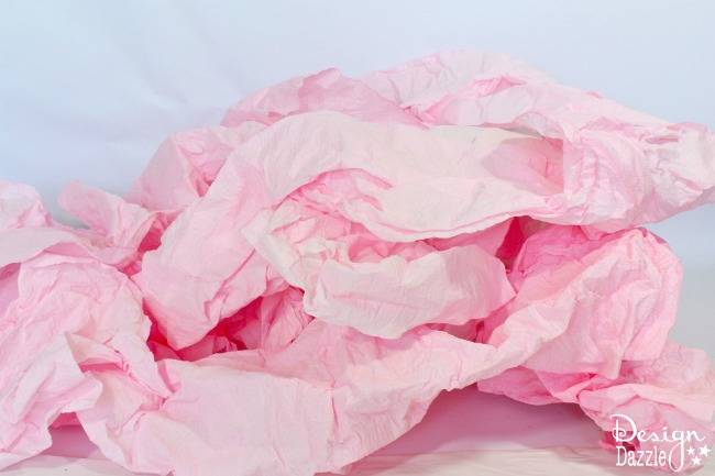 Step-by-step tutorial of how to transform a roll or paper towel to a fabulous paper ruffle garland on designdazzle.com! #DIYfairyparty #DIYpartydecor #papertowelgarland