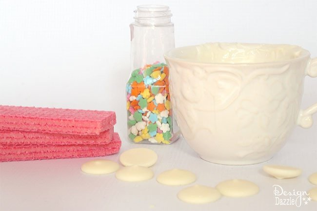All that is needed to make fairy cookies are strawberry wafers, white candy melts, and rainbow sprinkles. Easy sweet treat! See more on design dazzle.com #fairycookies #diyfairyparty