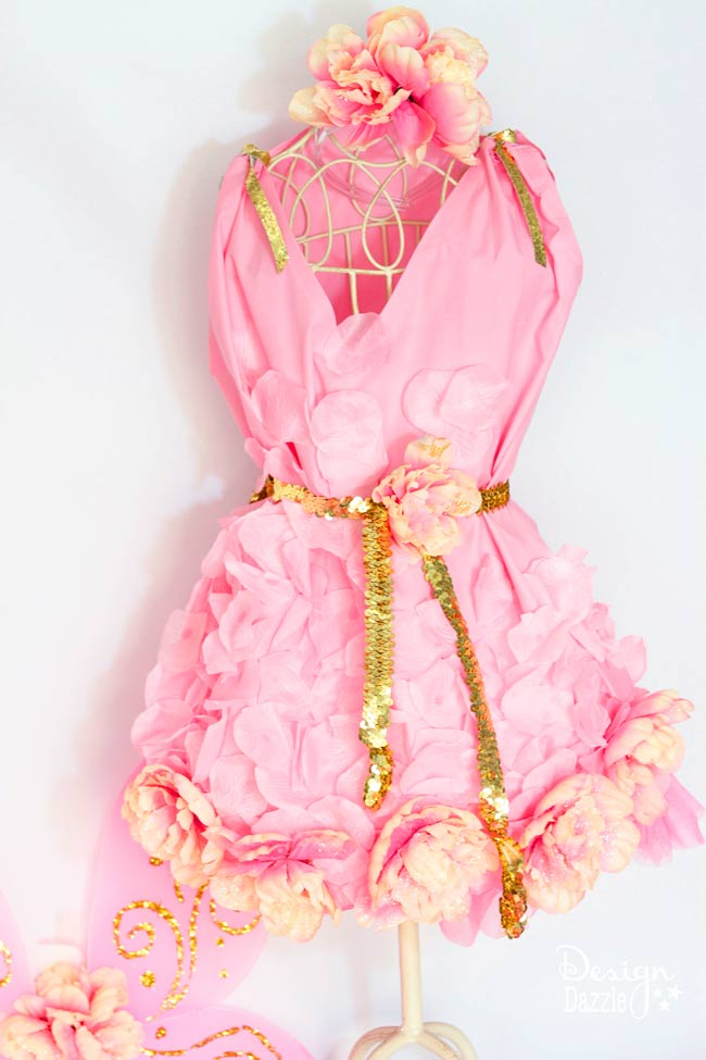 Can you believe this costume started as a pillowcase? Dollar store items were used to embellish this darling and inexpensive NO-SEW fairy costume! Design Dazzle #nosewcostume #fairycostume #pillowcasecostume
