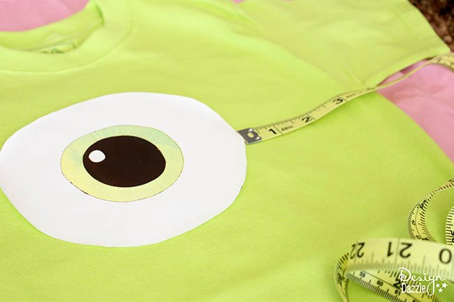 This QUICKLY and EASILY turns into a Mike Wazowski costume! A simple iron on -no sew, and can be made in about 15 minutes! Perfect for a last minute costume idea. See more at Design Dazzle. #diycostume #diyhalloween #mikewazowski