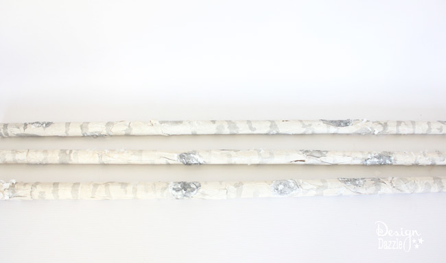 Step-by-step tutorial of how to make pool noodles into faux birch logs on Designdazzle.com. #diyChristmasdecor #poolnoodlediy