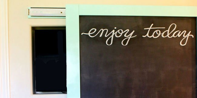 The kitchen TV is hidden in the wall and the chalkboard slides to cover!  | Design Dazzle