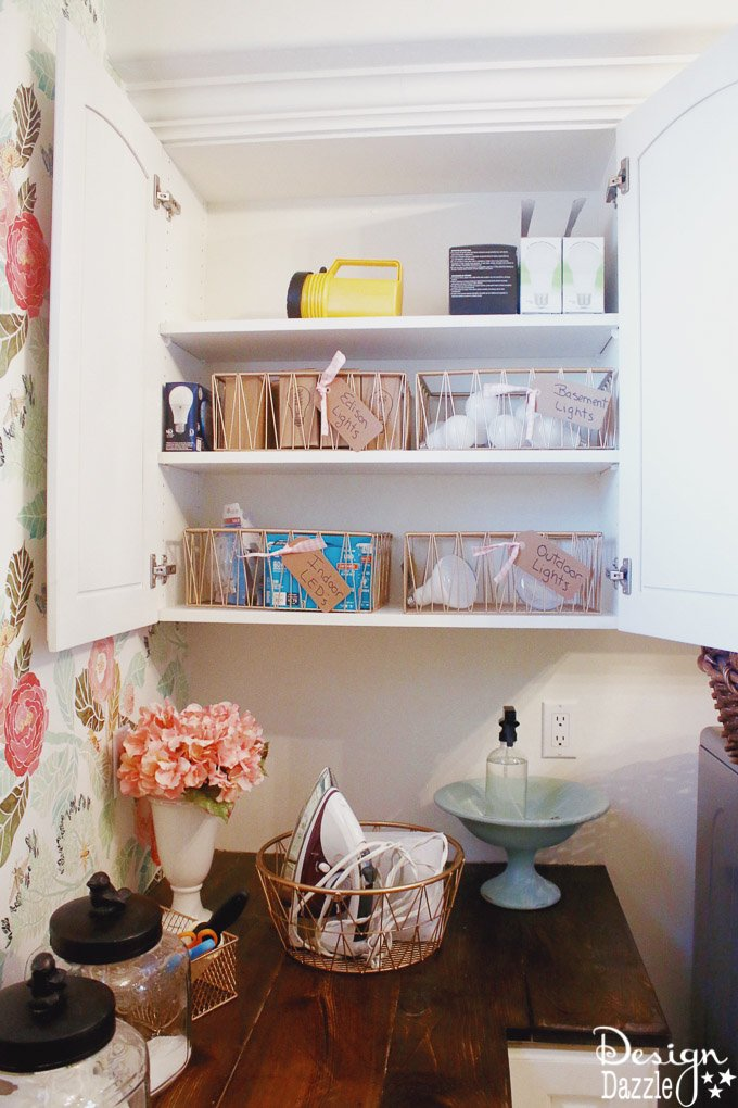 I'm showing you how to take your laundry room cabinet organization from drab to fab while on a budget! You will love these rose gold metal baskets! | Design Dazzle