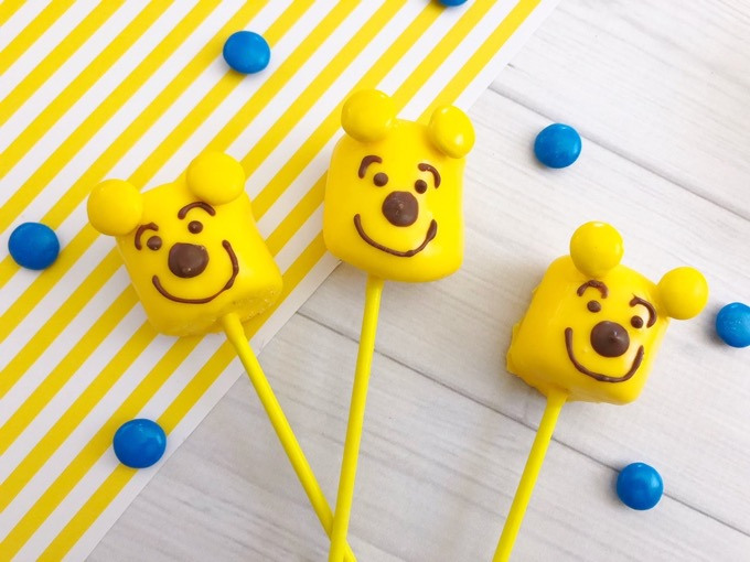 Make these pooh bear marshmallow pops in minutes! So easy and quick to make and super fun too! The kids will definitely enjoy making AND munching on them! - Design Dazzle