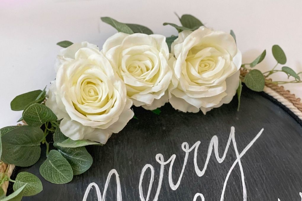 white roses are added to the pizza pan wreath